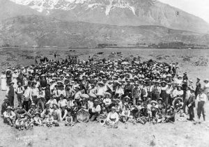 A black and white photo of a large group of students from 1907 dressed as cowboys after clearing out sagebrush from Orem. They pose in a large section of empty land in front of a mountain.