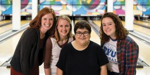 Chetty Pino stands surrounded by three of her buddies in the BYU Bowling Alley.