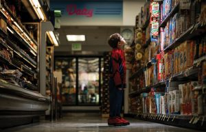 Child in Spiderman costume at the grocery store looking at products in an aisle.