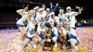 The BYU Women's basketball team gathers in front of the WCC trophy on a confetti-covered court.