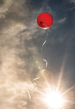A red balloon with a string attached ascends into a sunlit but cloudy sky.