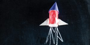 A paper rocket blasts off on a chalkboard with chalk exhaust drawn below it