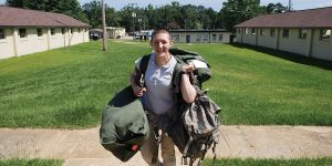 Anna Hodge stands in the middle of a courtyard, heavy canvas bags in both her hands and dangling off her shoulders. She is smiling broadly at the camera.