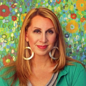 A headshot of Leslie Gradd against a fun painted floral backdrop.