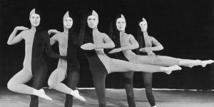 Five dancers dressed in full body tight suits split in half with gray and black take dancing poses for the camera.