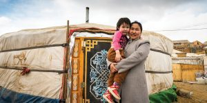 A Mongolian woman holds her daughter outside of their retrofitted ger, or traditional home.