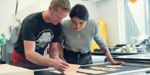 Brandon Gunn and a woman work on prints in a studio.