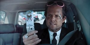 Mayhem, a character from AllState Insurance commercials, wears a black suit and tie and pink sunglasses on his foreheard. He holds a broken phone and has a bruised, scratched face.