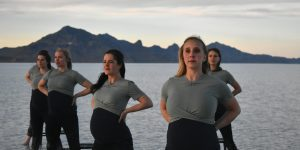 Five pregnant dancers stand looking outward with their hands on their hips.