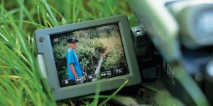 A video camera lies on the grass. On the screen of the camera, a young boy stands next to a wooden bridge stretching across a small stream.
