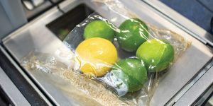 A biodegradable bag holds a lemon and four limes on top of a grocery store scanner.