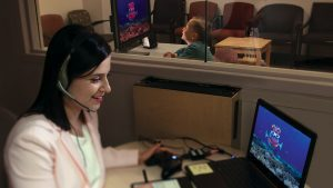 A woman interacts with an autistic boy via a computer animation of a talking fish.