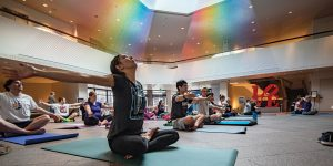 A woman sits on a yoga mat doing a yoga pose in the MOA.