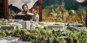 Two young boys admire a large 3-D-printed model of BYU campus from behind the glass.