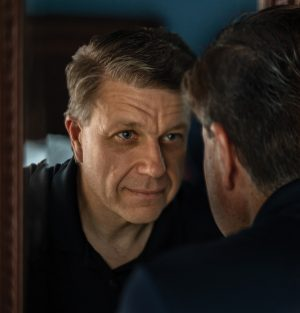 A handsome middle-aged man practices self-compassion by looking at his reflection in a mirror and imagining he is a person who cares deeply about himself and others.