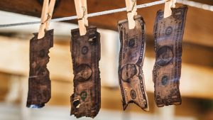 Fire-blackened money is attached to a line with clothespins.
