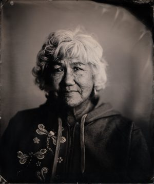 Black-and-white tintype photograph of a Native Alaskan woman in a jacket
