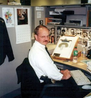Greg Bean sits in his office working on a composite sketch.