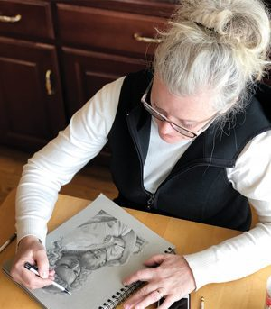 Jean draws a woman holding her child in colored pencil.