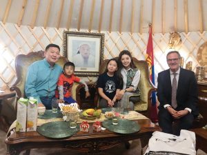 A man sits with a Mongolian family of one father, one mother, one son, and one daughter inside a traditional Mongolian yurt home.