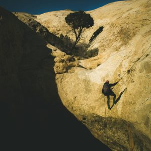 A man with a backpack facing away from the camera rappels down a cliff at Wild Horse Window.