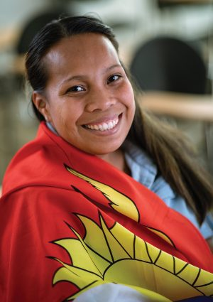 Tereua Kainitoka smiles with a Kiribati flag wrapped around her.