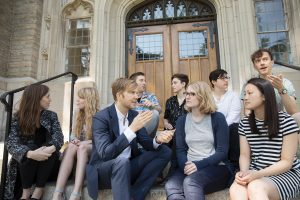 Zachary Davis and his Harvard team, which looks to be made up of students from Harvard, sit on the steps of an older building.