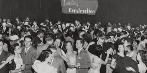A crowd of students in a 1950s-era picture dance in an assembly hall. The words