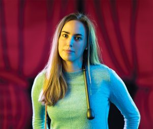 The 2019 BYU George H. Brimhall Memorial Essay Contest winner Hope Thomas stands in front of a red velvet curtain with a microphone draped around her shoulders. She tried stand-up comedy in her