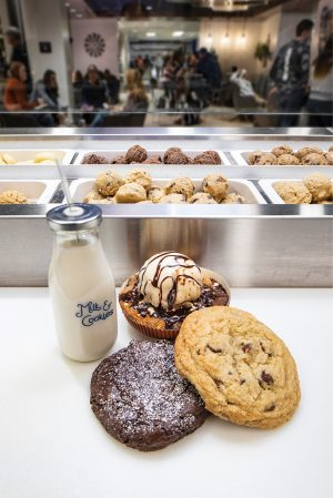 A jar of milk sits on a counter alongside two large cookies and a Cosmookie.