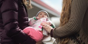 Two women—a caseworker and a foster mom—hold a baby girl and a handful of diapers in a gas station parking lot.