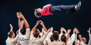 BYU Men's Chorus director Rosalind Hall is thrown in the air by a group of students.