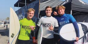 Three smiling Brigham Young Surf Team members hold surf boards and make the hang loose hand gesture.