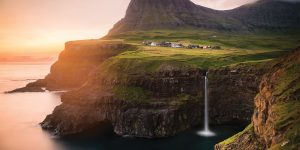 The Múlafossur Waterfall in the Faroe Islands. The sky is pink and orange, with the glow of dusk illuminating parts of the cliff's edge. On the right, a few houses sit atop a green field of grass, and then at the bottom half edge of the cliff, a silky waterfall.