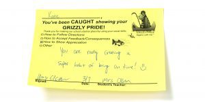 A yellow note written by a teacher to praise a student for good behavior. It says,