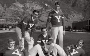 Five young male cheerleaders from 1968 wear plaid pants and sweaters with a big