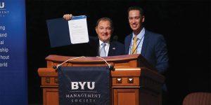 Gary Herbert stands at a podium, holding up a document, beside Joshua Flade.