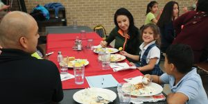 Parents and students sit at a dinner table together in the Homework Diner.