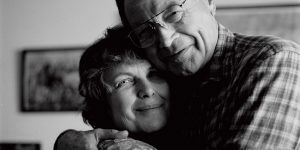 A smiling older couple embrace.