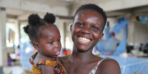 A young mother holds her toddler and smiles at the camera. The child had reconstructive surgery for a cleft palate.