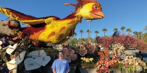 A woman in a light blue t-shirt and black pants stands in front of a parade float she created. The float is a creation of nature, with green grass, gray stones, yellow, pink, and purple flowers. Sitting atop the float is a yellow and orange bird with wings spread wide.
