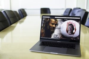 A laptop in an empty conference room with a Zoom screen showing BYU MBA student Trevor Lemmons dressed up as Wilson the volleyball from the movie Cast Away, with a Zoom background showing Tom Hanks's character beside him.