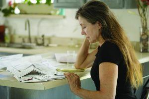 A woman sits at her kitchen counter looking thoughtfully at a stack of bills.