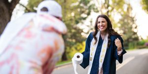 A female BYU grad smiles while wearing a graduation stole made from toilet paper with the word
