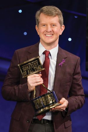 Ken Jennings III stands smiling proudly, holding the trophy declaring him the Jeopardy! GOAT.