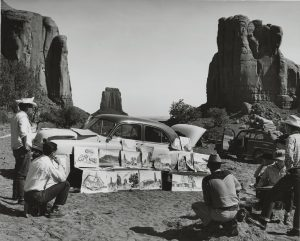 Art students look at a collection of art pieces leaning against a car at the base of a red-rock landscape.