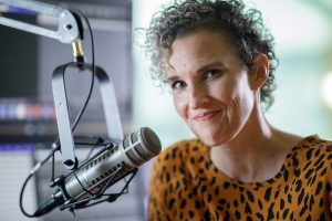 A portrait of Top of Mind host Julie Rose next to a microphone.