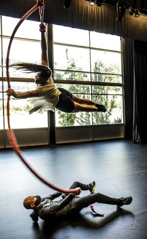 Adam Dyer lays on the floor, holding a long rope that twirls dancer Mariah Sainsbury parallel to the floor.