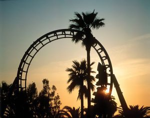 Roller coaster loop silhouetted at sunset