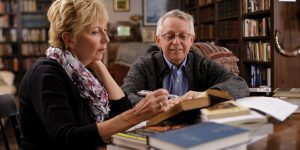 Fiona and Terryl Givens sit side by side at a table in their home library. Their table is covered in books. Fiona holds a pen in hand, about to mark a passage from a book.